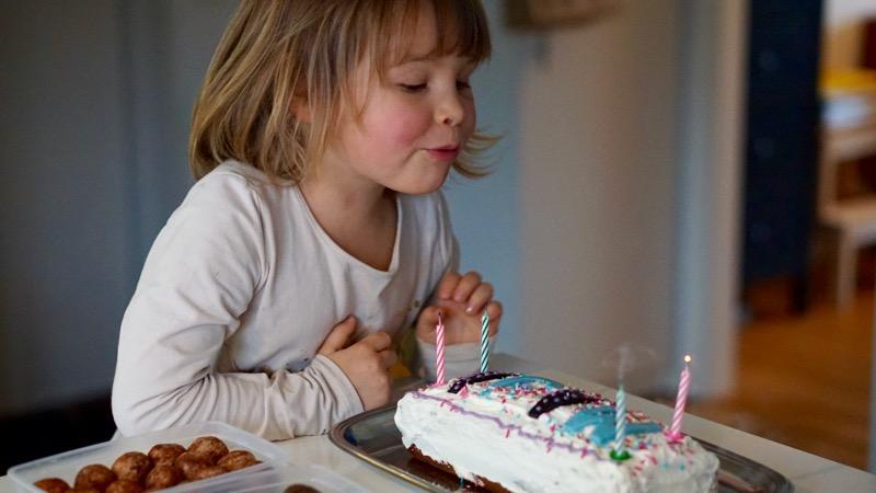 Blåser ut ljusen på tårtan